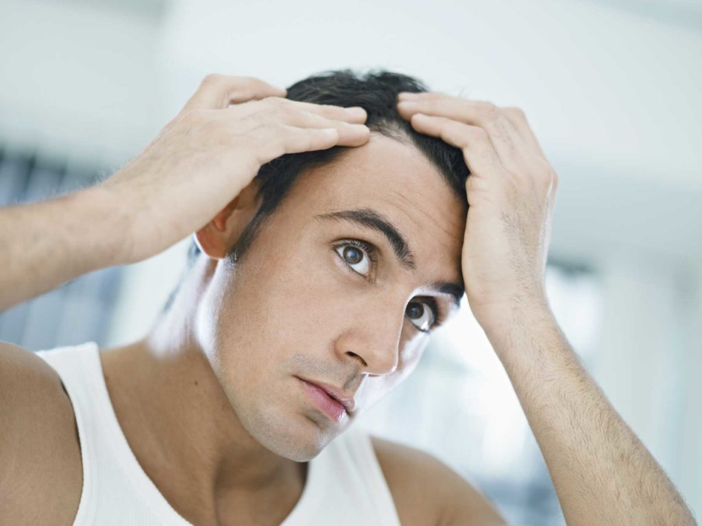 man checking to see is hair is thinning